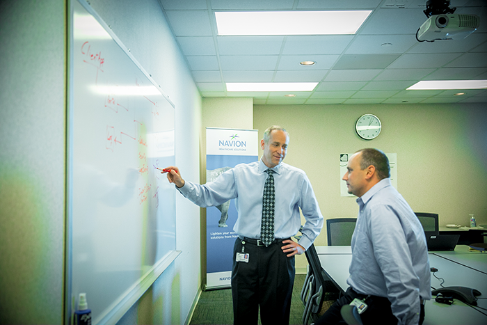 John Peasley & a Navion employee at a whiteboard looking at data